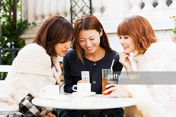 魅力的な日本の女性、東京のストリートカフェ」の携帯電話