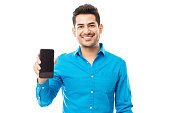 Portrait of attractive male smiling while holding smartphone against white background