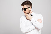 Attractive man with black hair and beard wearing white shirt with bowtie and sunglasses at gray studio background, portrait, copy space.