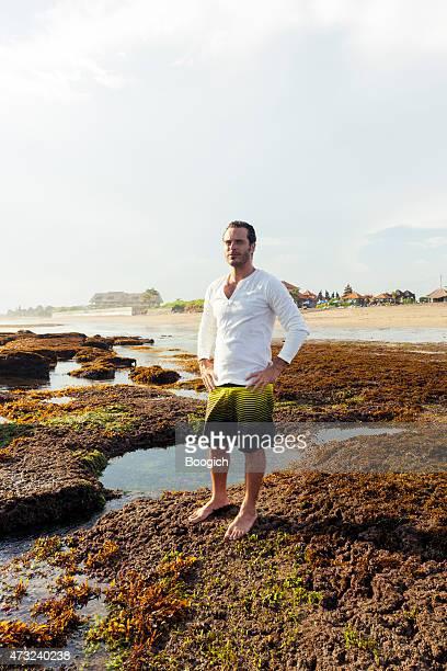 Attractive Man Enjoys View at Scenic Bali Beach Travel Destination