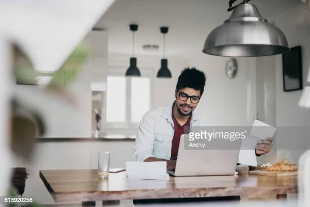 Attraktiver Mann ist Laptop verwendet, um Rechnungen online bezahlen
