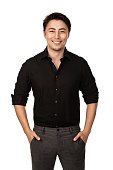 Attractive man in a black shirt and grey pants, standing with a big smile against a white background,