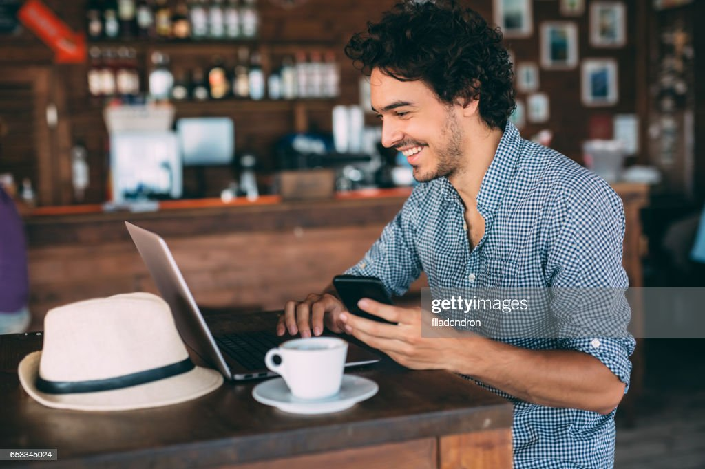 Attractive man surfing the net at the cafe : Stock Photo