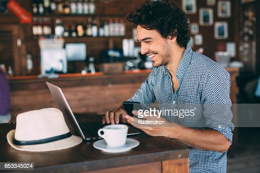 Attractive man surfing the net at the cafe : Bildbanksbilder