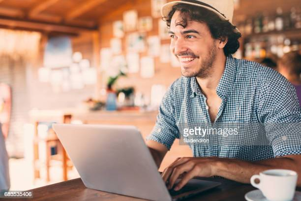 Attractive man using a laptop at the cafe