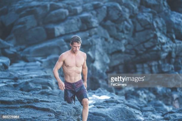Attraktiver Mann zu Fuß entlang der Klippen im Badeanzug