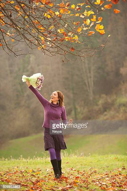Attractive Mature Woman with Bouquet of Flowers on Autumn Meadow