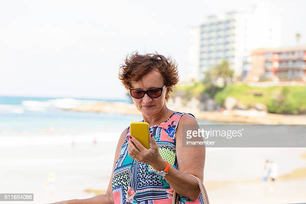 Attractive mature woman with sunglasses looking at her phone, outdoor