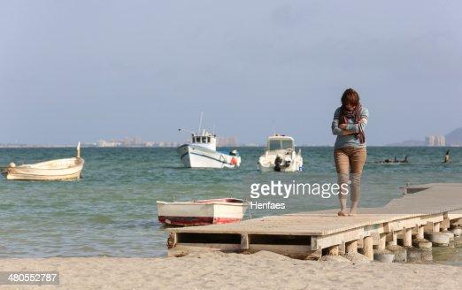 Atractiva mujer de edad media cuidadosamente camina por el muelle junto a la playa : Foto de stock