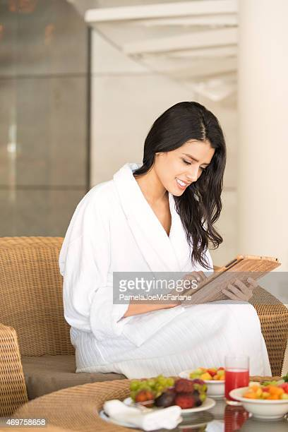 Attractive Middle Eastern Woman with Computer Tablet Eating Spa Breakfast