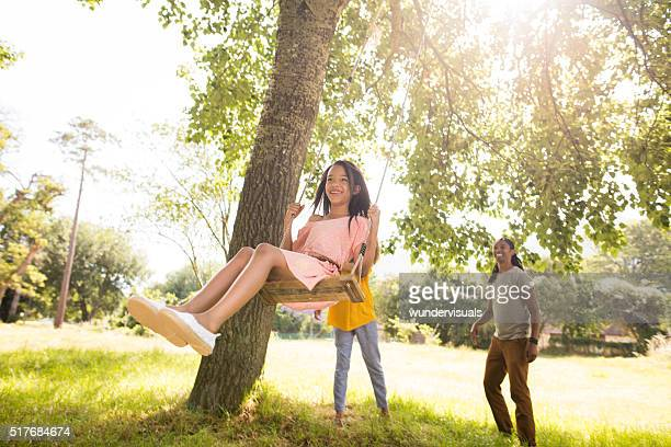 Attractive mother and father takes daughter to park to swing.