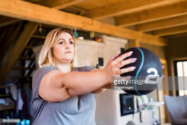 Attractive overweight woman at home exercising with medicine ball, doing squats.