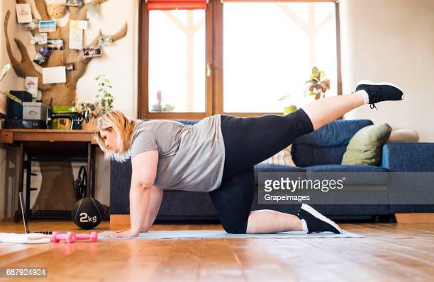Attractive overweight woman at home, laptop in front of her, working out on mat according to video, lifting leg.