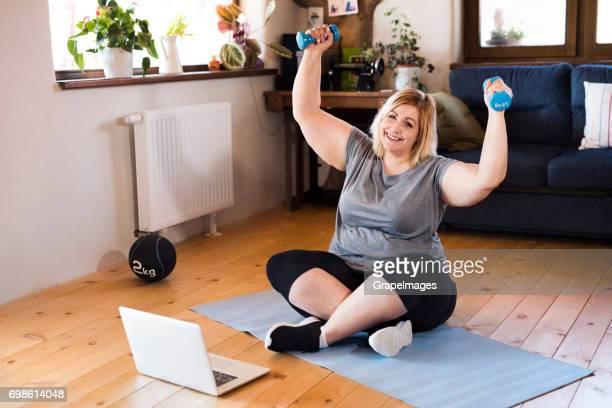 Attraktive übergewichtige Frau zu Hause, Laptop vor ihr Workout mit Hantel nach Video.