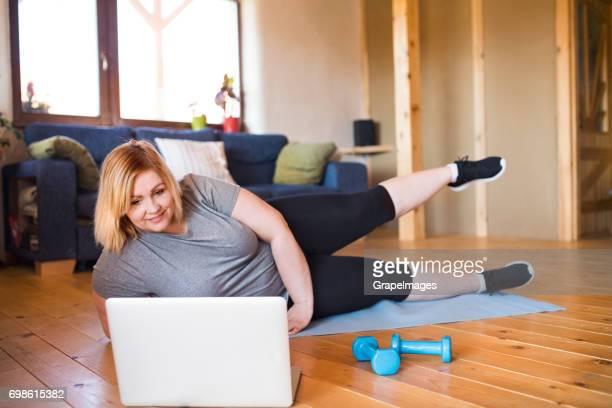 Attraktive übergewichtige Frau zu Hause, Laptop vor ihr, arbeiten auf Matte nach Video, Bein anheben.