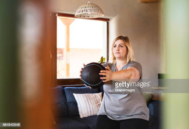 Attractive overweight woman at home working out with medicine ball, doing squats.