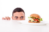 Cheerful guy is hiding behind a table and peeping through it. He is looking at an unhealthy hamburger with desire. Isolated on background