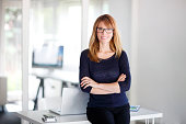 Portrait of middle aged executive businesswoman standing at workstation in front of desk.