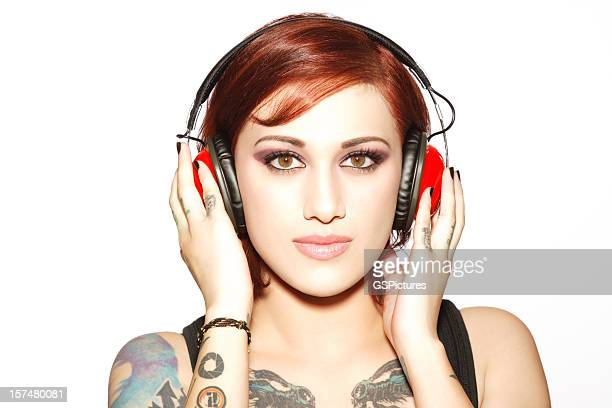 Attractive Redhead Listening to music on Headphones. Isolated.