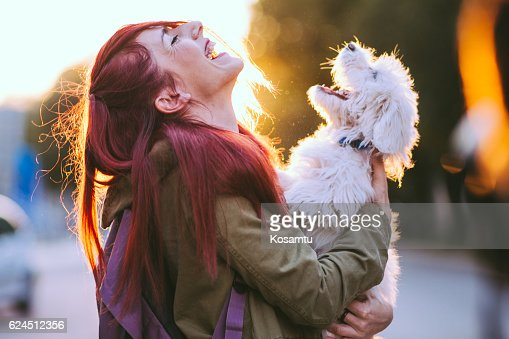 Attractive Redheaded Girl and White Puppy Smiling Together : Stock-Foto