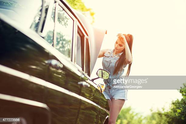 Attractive Retro Woman Fixing the Old Timer Car at Sunset