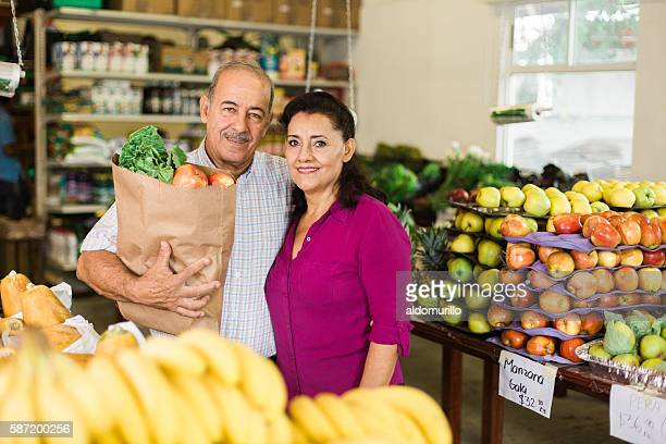 Attractive senior couple carrying groceries