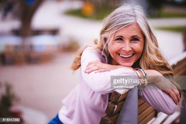 笑いと公園のベンチに座っている魅力的な年配の女性