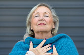 Attractive senior woman savoring the moment standing with her eyes closed and head tilted back with a serene expression as she clasps her chest with her hands