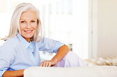 Portrait of attractive senior woman smiling while relaxing on sofa at home. Horizontal shot.