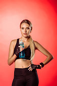 attractive sportswoman holding sport bottle with water and looking at camera isolated on red