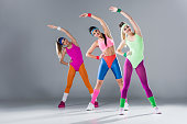 attractive sporty girls in bodysuits training at aerobics workout on grey