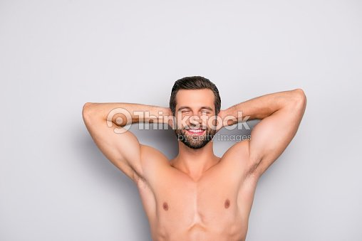 Attractive, stunning, manly, smiling macho isolated on gray background, having two arms behind the head and closed eyes, showing his shaven armpits - wellness, wellbeing concept : Stock Photo