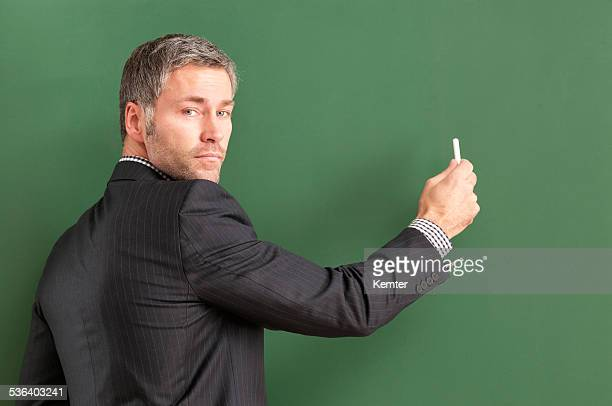attractive teacher with grey hair writing at blackboard
