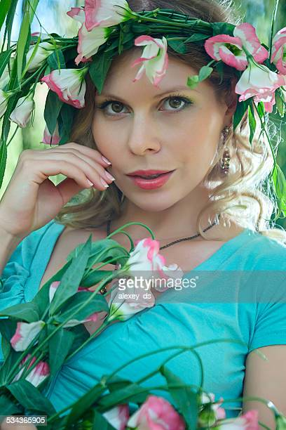 Attractive tender woman with wreath on head and pink flowers