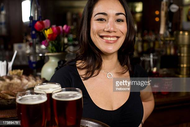 attractive waitress holding three beers on a tray and smiling
