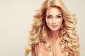 Attractive woman blonde with elegant hairstyle. Example of long,dense and curly hair.