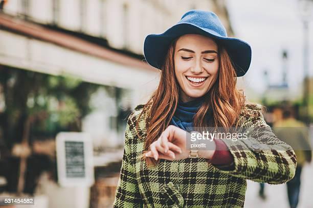 Attraente donna controlla il Suo orologio sulla strada
