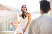 Attractive woman drinking cocktail and enjoying her summer vacation.Drinking refreshing drink and smiling to a man.Flirting and seduction.Man approaching to a woman.Attracted people.One night standAtt