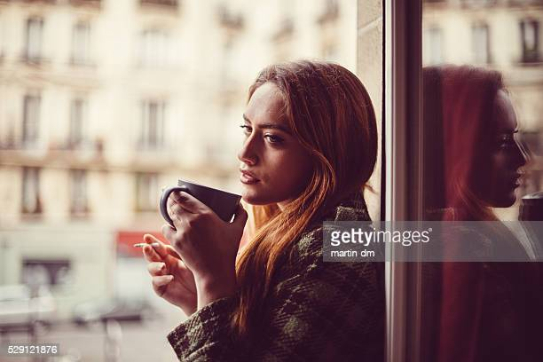 Attractive woman drinking coffee on the window
