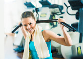 Attractive woman exercising at gym, biceps workout on a machine.