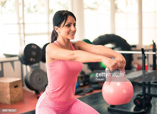 Attractive woman exercising with kettle bell