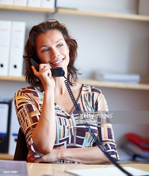 Attraktive Frau hält eine Telefonhörer im Büro-Schreibtisch