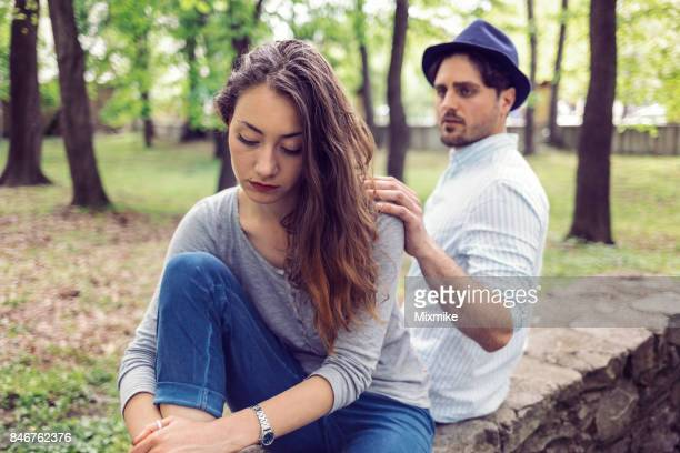 Attractive woman in the park looking troubled and unhappy and sitting away from her boyfriend