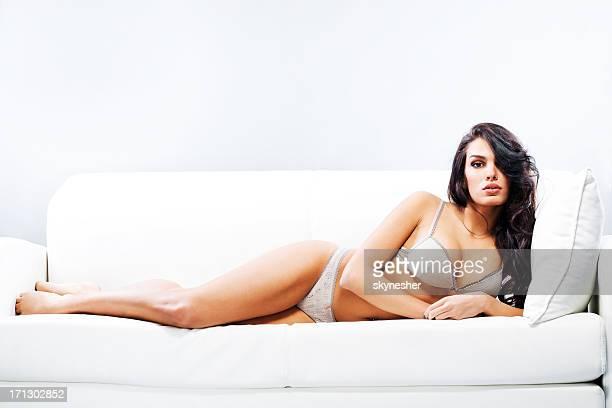 Atraente mulher Deitada no sofá no interior.