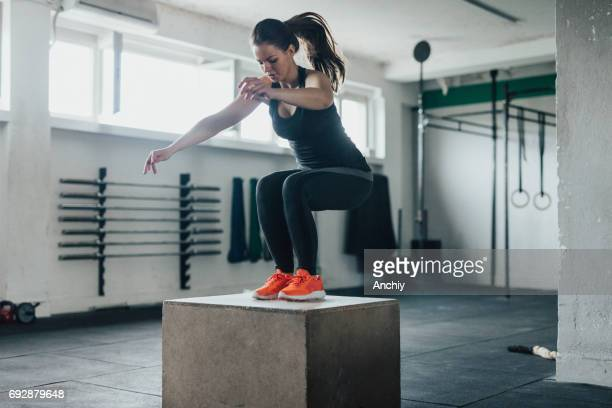 Attractive woman jump on a crate in a gym