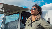 Attractive woman pilot wearing sunglasses standing in the sunshine on an airfield resting against her small private airplane