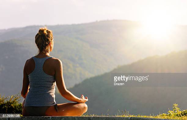 Attractive woman practices yoga and meditation in nature during summer