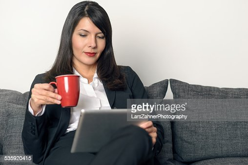 Attractive woman reading on a tablet pc : Stock Photo