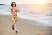 Attractive woman runner runs on tropical sand beach in summer. Healthy lifestyle and running sport concept.