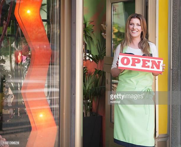 魅力的な女性のショップオーナー保持 sing オープンいたします。